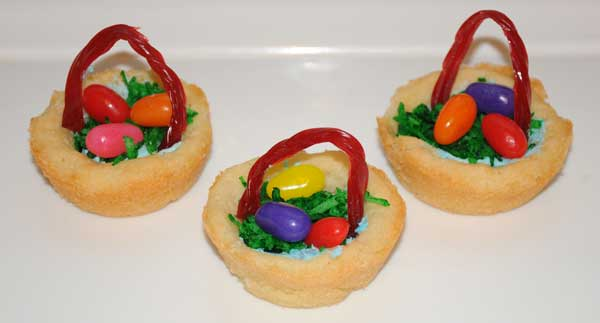 Easter Desserts For Kids that look like easter baskets made from cookies, coconut, licorice, and jelly beans