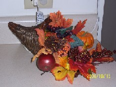 picture of fall centerpiece with leaves, pumpkins, squash, and fruit.