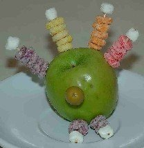 Turkey made out of an apple and cereal for feathers for kids Thanksgiving recipes
